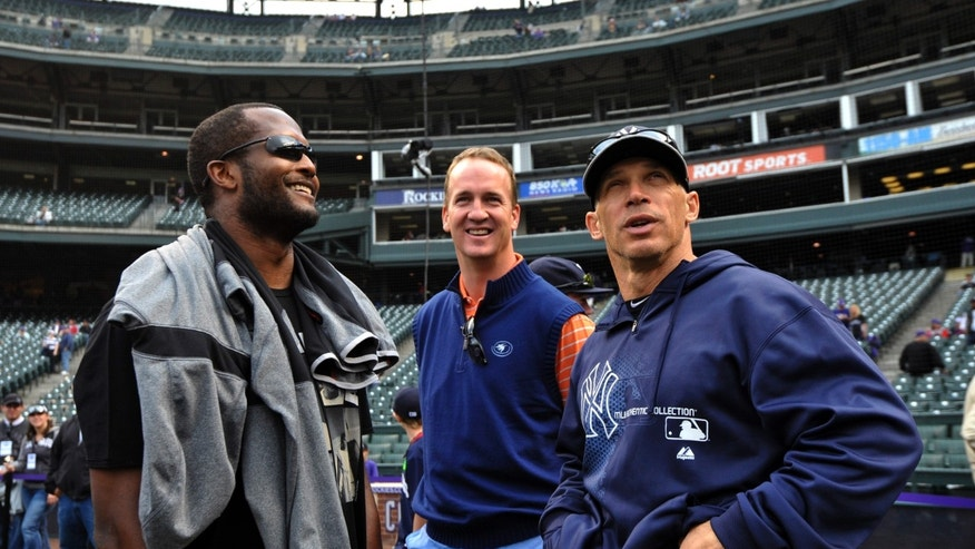 New York Yankees manager Joe Girardi, right, talks with Denver Broncos players  Champ Bailey, left, and Peyton Manning,center,  during batting practice before a baseball game between the New York Yankees and the Colorado Rockies on Tuesday, May 7, 2013, in Denver. (AP Photo/Jack Dempsey)