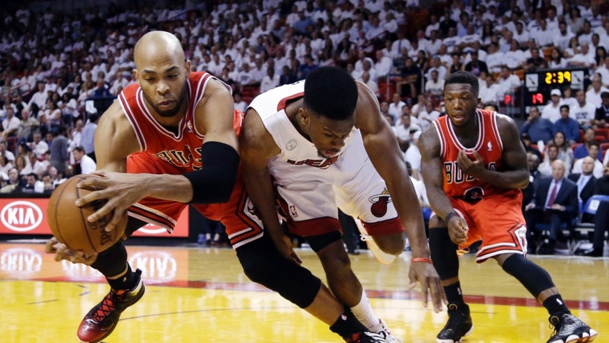 Chicago Bulls forward Taj Gibson, left, and Miami Heat guard Norris Cole battle for a loose ball as guard Nate Robinson, far right, watches during the first half of Game 2 of their NBA basketball playoff series in the Eastern Conference semifinals, Wednesday, May 8, 2013, in Miami. (AP Photo/Lynne Sladky)