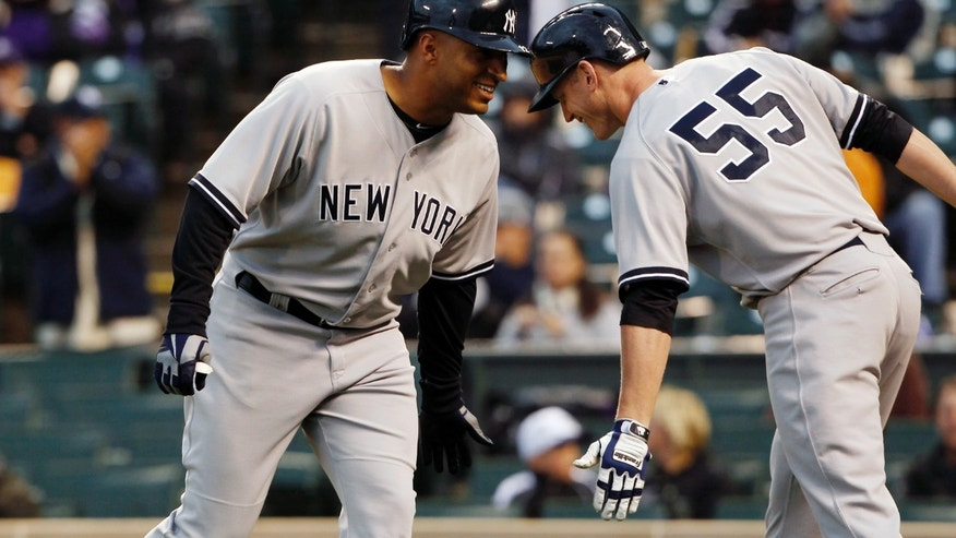 New York Yankees' Vernon Wells, left, is congratulated by teammate Lyle Overbay after hitting a two-run home run against the Colorado Rockies in the first inning of a baseball game in Denver on Wednesday, May 8, 2013. (AP Photo/David Zalubowski)