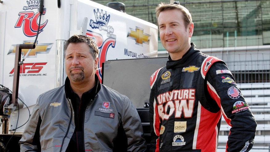 Andretti Autosport team owner Michael Andretti, left, and NASCAR driver Kurt Busch wait for the start of a testing session at the Indianapolis Motor Speedway in Indianapolis, Thursday, May 9, 2013. Busch was driving an Indycar for the first time during the test. (AP Photo/AJ Mast)