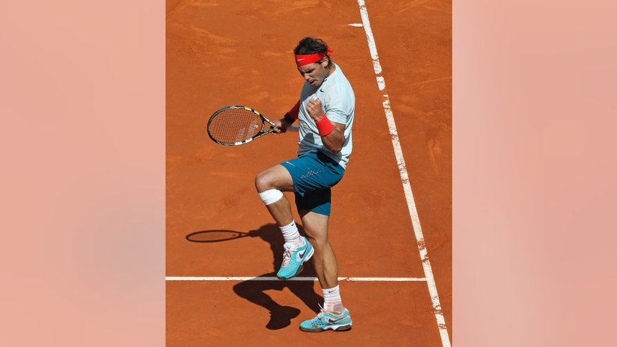 Rafael Nadal from Spain celebrates winning a point during the match against Mikhail Youzhny from Russia at the Madrid Open tennis tournament, in Madrid, Thursday, May 9, 2013. (AP Photo/Andres Kudacki)