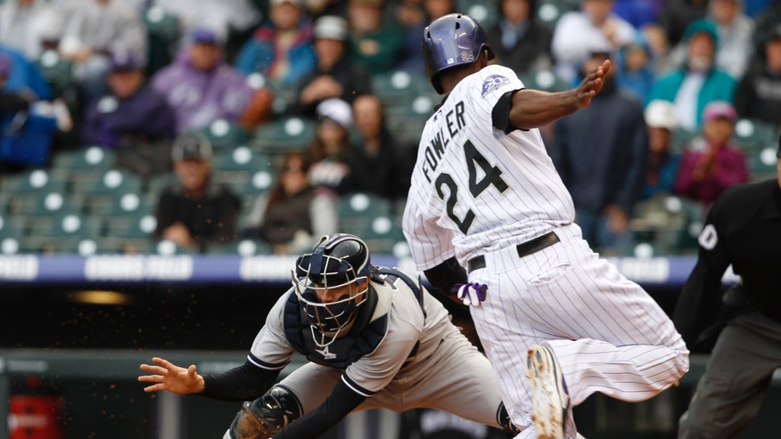 New York Yankees catcher Chris Stewart, left, fields the throw from the outfield as Colorado Rockies' Dexter Fowler scores on a sacrifice fly hit by Carlos Gonzalez in the first inning of a baseball game in Denver on Thursday, May 9, 2013. (AP Photo/David Zalubowski)