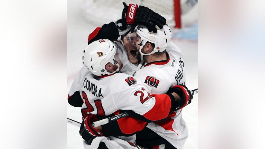Ottawa Senators center Kyle Turris (7) celebrates with teammates Erik Condra (22) and Chris Phillips (4) after scoring the fourth goal against the Montreal Canadiens during the second period of Game 5 first round NHL hockey Stanley Cup playoff series, Thursday, May 9, 2013, in Montreal. (AP Photo/The Canadian Press, Ryan Remiorz)