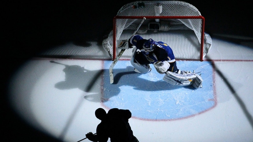 St. Louis Blues goalie Brian Elliott, top, warms up as a teammate skates past before Game 5 in a first-round NHL hockey Stanley Cup playoff series, against the Los Angeles Kings on Wednesday, May 8, 2013, in St. Louis. (AP Photo/Jeff Roberson)