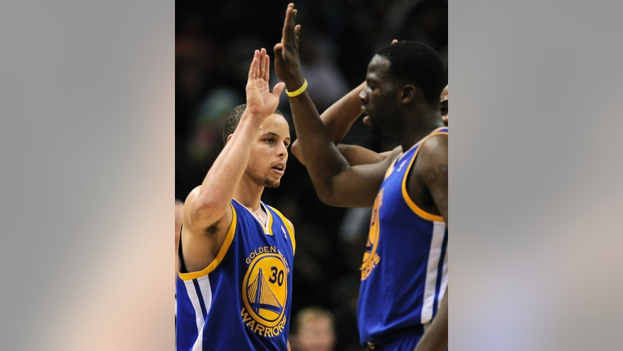 Golden State Warriors' Stephen Curry, left, celebrates with teammate Draymond Green at the end of Game 2 of the Western Conference semifinal NBA basketball playoff series against the San Antonio Spurs, Wednesday, May 8, 2013, in San Antonio. Golden State won 100-91.(AP Photo/Darren Abate)