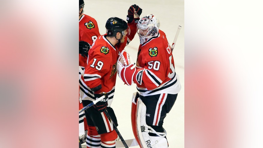 Chicago Blackhawks goalie Corey Crawford, right, celebrates with Jonathan Toews after the Blackhawks defeated the Minnesota Wild 5-1 in Game 5 of an NHL hockey Stanley Cup first-round playoff series in Chicago, Thursday, May 9, 2013.  (AP Photo/Nam Y. Huh)