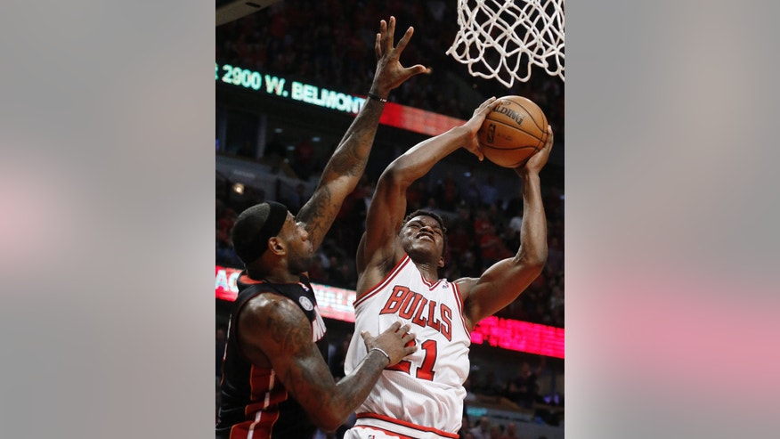 Chicago Bulls small forward Jimmy Butler (21) shoots against Miami Heat small forward LeBron James (6) during the second half of Game 3 of an NBA basketball playoffs Eastern Conference semifinal on Friday, May 10, 2013, in Chicago. (AP Photo/Charles Rex Arbogast)