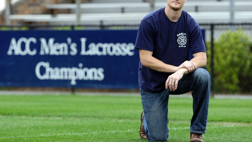 In this photo taken Wednesday, May 8, 2013, Duke lacrosse player Casey Carroll poses for a portrait on the lacrosse playing field at Duke University in Durham, N.C. The former All-American defenseman is now a husband, father, former Army Ranger, combat veteran and graduate student hoping to return for a final unused year of eligibility. A knee injury prevented that this year, meaning the 28-year-old Carroll, the last active member of the 2006 team scarred by false rape allegations against three players , will be here for Duke's NCAA opener Sunday only to back the Blue Devils and feel close to the sport he hopes to play again next year. (AP Photo/Gerry Broome)