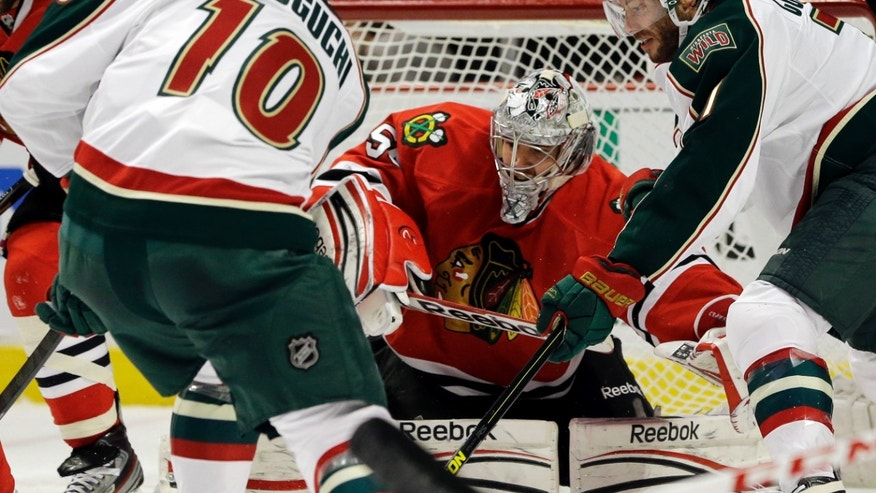 Chicago Blackhawks goalie Corey Crawford (50) blocks a shot by Minnesota Wild's Devin Setoguchi (10) as Matt Cullen (7), right, looks on during the first period of Game 5 of an NHL hockey Stanley Cup first-round playoff series in Chicago, Thursday, May 9, 2013. (AP Photo/Nam Y. Huh)