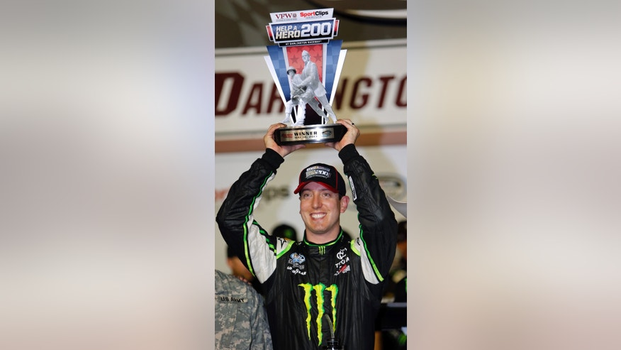 Kyle Busch holds the trophy in Victory Lane after winning the NASCAR Nationwide series auto race at Darlington Raceway, Friday, May 10, 2013, in Darlington, S.C.  (AP Photo/Mic Smith)