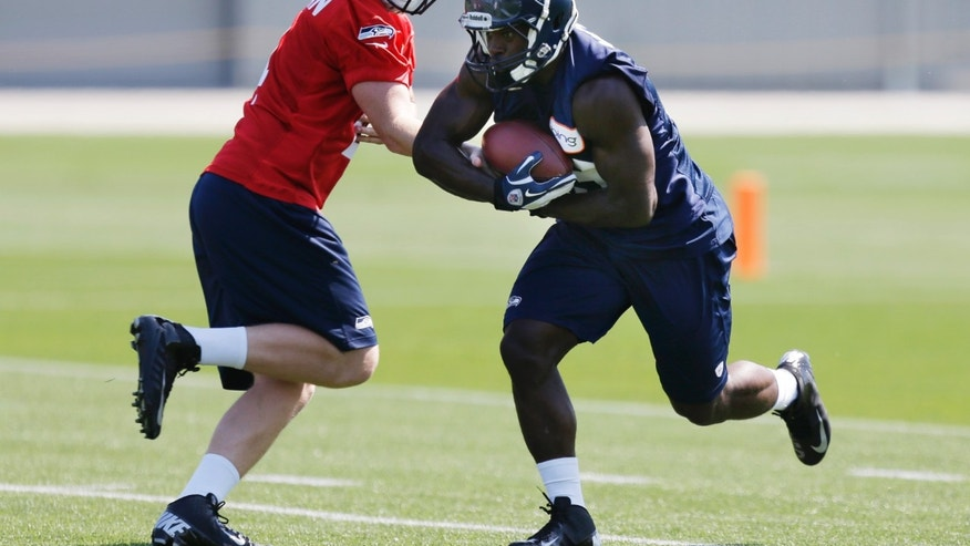 Seattle Seahawks' quarterback Casey Brockman, left, hands off to running back Christine Michael, right, during practice drills at Seattle Seahawks NFL football Rookie Minicamp, Friday, May 10, 2013, in Renton, Wash. (AP Photo/Ted S. Warren)