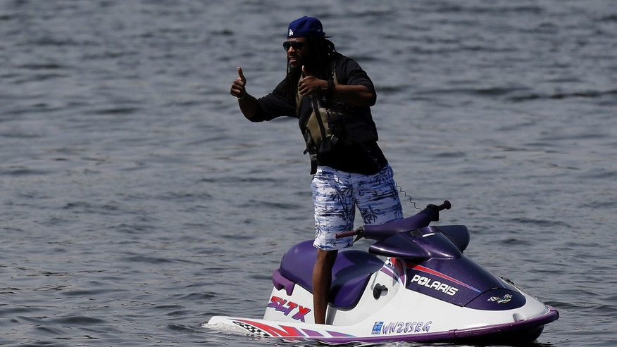 Seattle Seahawks cornerback Richard Sherman gestures offshore from NFL football rookie minicamp from a personal watercraft on Lake Washington, Friday, May 10, 2013, in Renton, Wash. (AP Photo/Ted S. Warren)