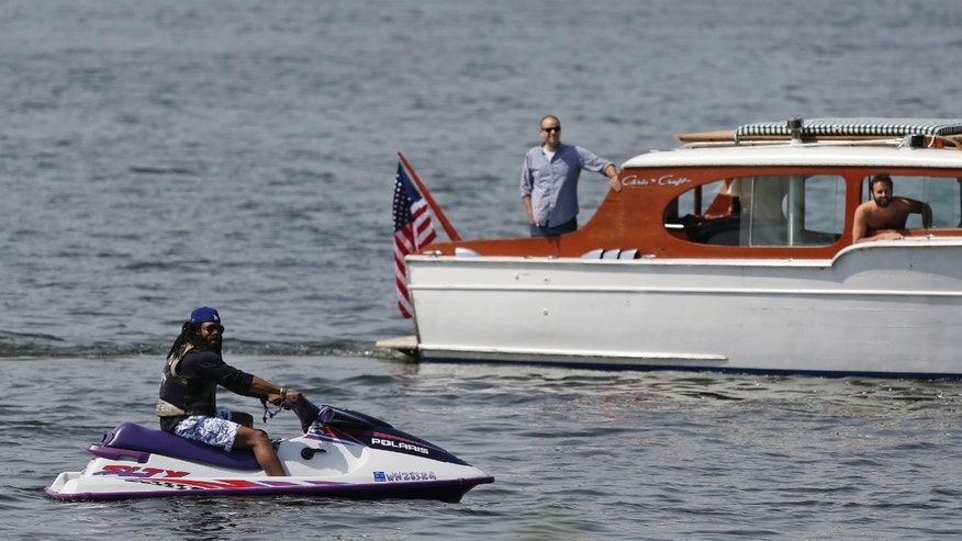 Seattle Seahawks cornerback Richard Sherman, left, watches the NFL football team's rookie minicamp from a personal watercraft on Lake Washington, Friday, May 10, 2013, in Renton, Wash. (AP Photo/Ted S. Warren)