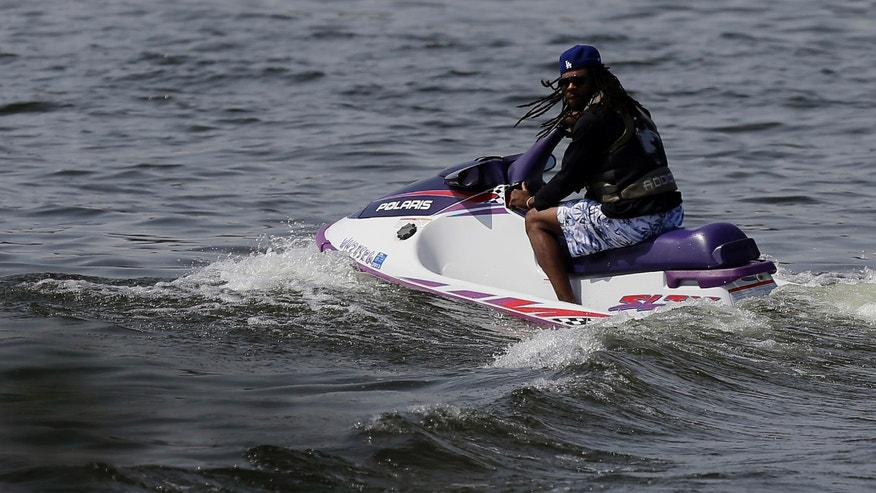 Seattle Seahawks cornerback Richard Sherman watches the NFL football rookie minicamp from a personal watercraft on Lake Washington, Friday, May 10, 2013, in Renton, Wash. (AP Photo/Ted S. Warren)