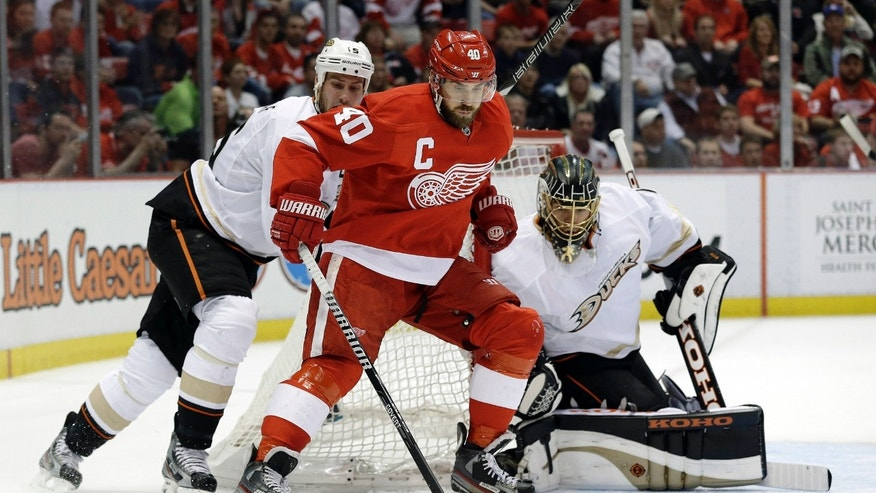 Detroit Red Wings center Henrik Zetterberg (40) protects the puck from Anaheim Ducks center Ryan Getzlaf (15) as goalie Jonas Hiller (1), of Switzerland, looks on in the second period in Game 6 of a first-round NHL hockey Stanley Cup playoff series in Detroit, Friday, May 10, 2013. (AP Photo/Paul Sancya)
