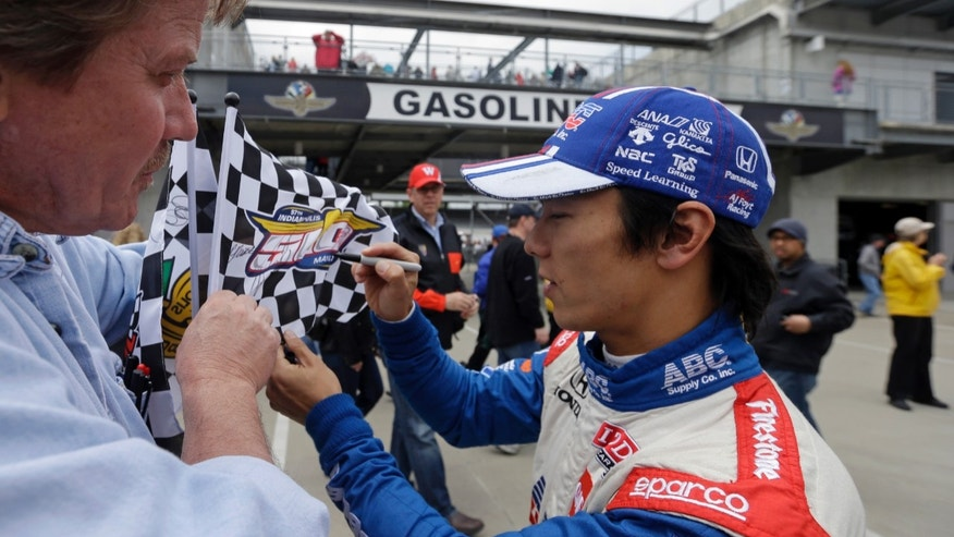 Takuma Sato, of Japan, signs a flag for race fan Scot West as leaves the pit area on the opening day of practice for the IndyCar Indianapolis 500 auto race at the Indianapolis Motor Speedway in Indianapolis, Saturday, May 11, 2013. (AP Photo/Darron Cummings)
