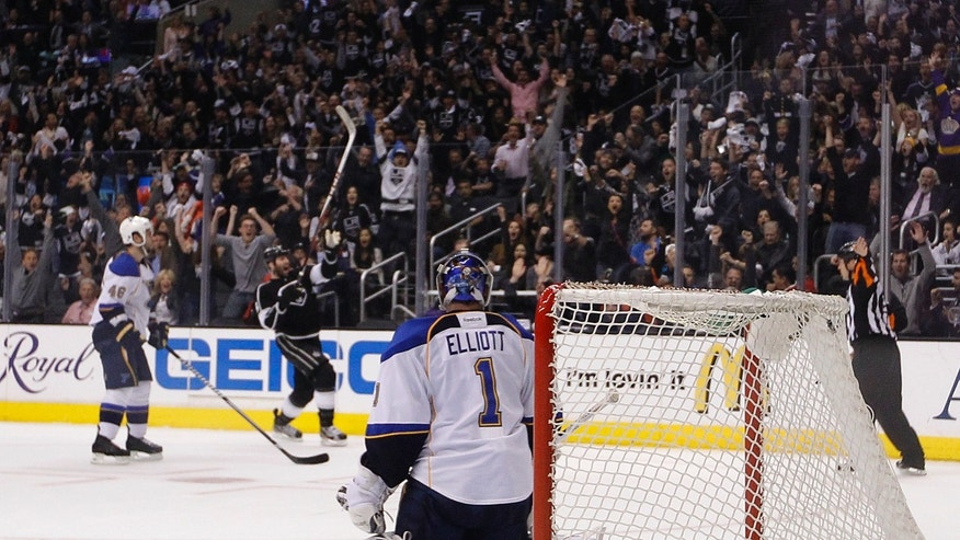 St. Louis Blues goalie Brian Elliott, center, watches Los Angeles Kings' Dustin Penner, background center, celebrate his goal during the second period in Game 6 of a first-round NHL hockey Stanley Cup playoff series in Los Angeles, Friday, May 10, 2013. (AP Photo/Jae C. Hong)