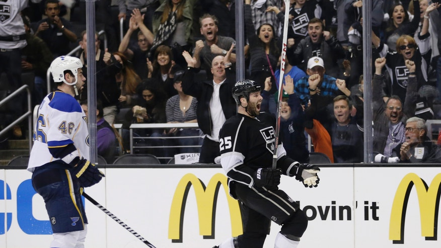 Los Angeles Kings' Dustin Penner, center, celebrates his goal as he skates past St. Louis Blues' Roman Polak, of Czech Republic, during the second period in Game 6 of a first-round NHL hockey Stanley Cup playoff series in Los Angeles, Friday, May 10, 2013. (AP Photo/Jae C. Hong)