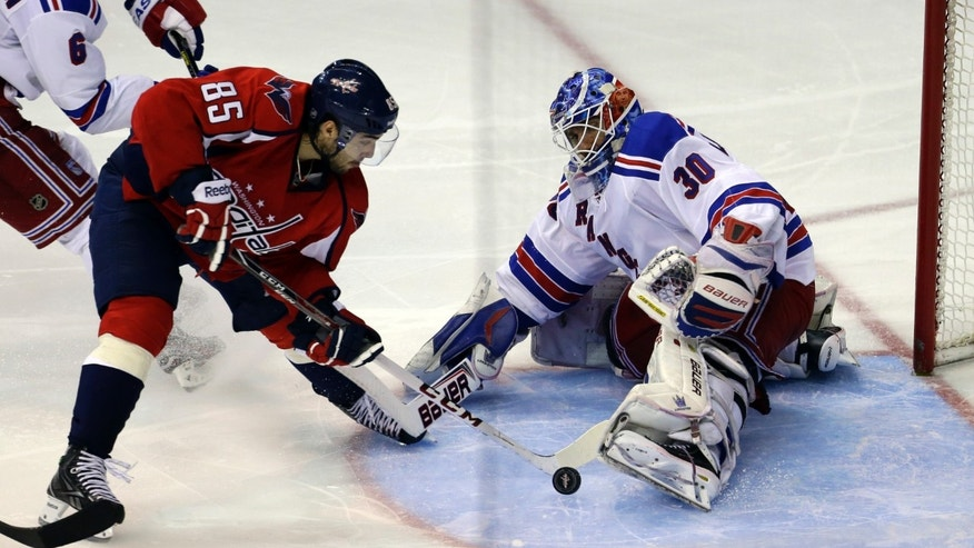 New York Rangers goalie Henrik Lundqvist (30), from Sweden, makes a save on a shot by Washington Capitals center Mathieu Perreault (85) in overtime of Game 5 first-round NHL Stanley Cup playoff hockey series, Friday, May 10, 2013, in Washington. The Capitals won 2-1, in overtime. (AP Photo/Alex Brandon)