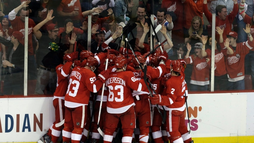 Detroit Red Wings players celebrate Henrik Zetterberg's goal in overtime against the Anaheim Ducks in Game 6 of a first-round NHL hockey Stanley Cup playoff series in Detroit, Friday, May 10, 2013. Detroit won 4-3. (AP Photo/Paul Sancya)