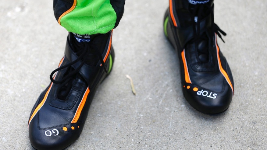 "The shoes of race drive James Hinchcliffe display ""GO"" for the gas and  ""STOP"" for the brakes as he stands in the pit area during practice for the Indianapolis 500 auto race at the Indianapolis Motor Speedway in Indianapolis, Sunday, May 12, 2013. (AP Photo/Darron Cummings)"