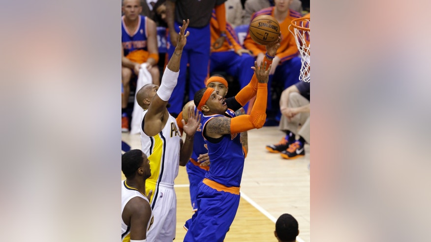 New York Knicks forward Carmelo Anthony, right, is fouled as he shoots by Indiana Pacers forward David West during the first half of Game 3 of the Eastern Conference semifinal NBA basketball playoff series in Indianapolis, Saturday, May 11, 2013.  (AP Photo/Michael Conroy)