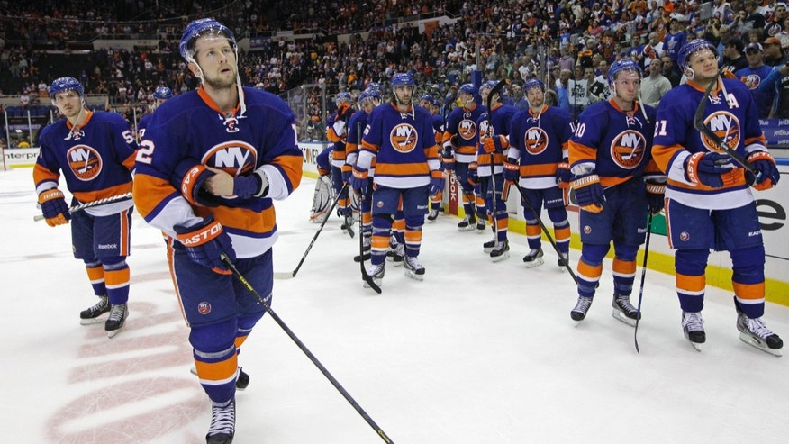 New York Islanders defenseman Mark Streit (2) and teammates react after the Pittsburgh Penguins defeated Islanders 4-3 in overtime of Game 6 of a first-round NHL Stanley Cup playoff hockey series, in Uniondale, N.Y., Saturday, May 11, 2013. The Penguins advanced to the Eastern Conference semifinals. (AP Photo/Kathy Willens)
