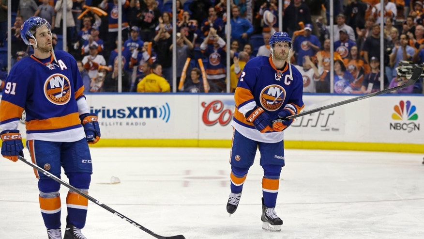 New York Islanders center John Tavares (91) and defenseman Mark Streit (2) react as the crowd applauds Islanders' season after the Pittsburgh Penguins defeated the Islanders 4-3 in overtime of Game 6 of a first-round NHL Stanley Cup playoff hockey series in Uniondale, N.Y., Saturday, May 11, 2013. The Penguins advanced to the Eastern Conference semifinals. (AP Photo/Kathy Willens)