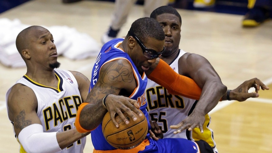 New York Knicks forward Amar'e Stoudemire, center, is tied up by Indiana Pacers center Roy Hibbert, right, and forward David West during the second half of Game 3 of the Eastern Conference semifinal NBA basketball playoff series in Indianapolis, Saturday, May 11, 2013.  (AP Photo/Michael Conroy)