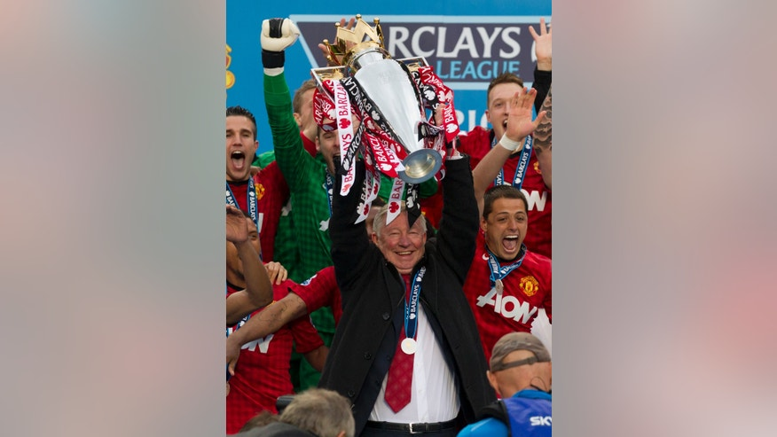 Manchester United's manager Sir Alex Ferguson lifts the premier league trophy after his last home game in charge of the club, their English Premier League soccer match against Swansea City, at Old Trafford Stadium, Manchester, England, Sunday May 12, 2013. (AP Photo/Jon Super)