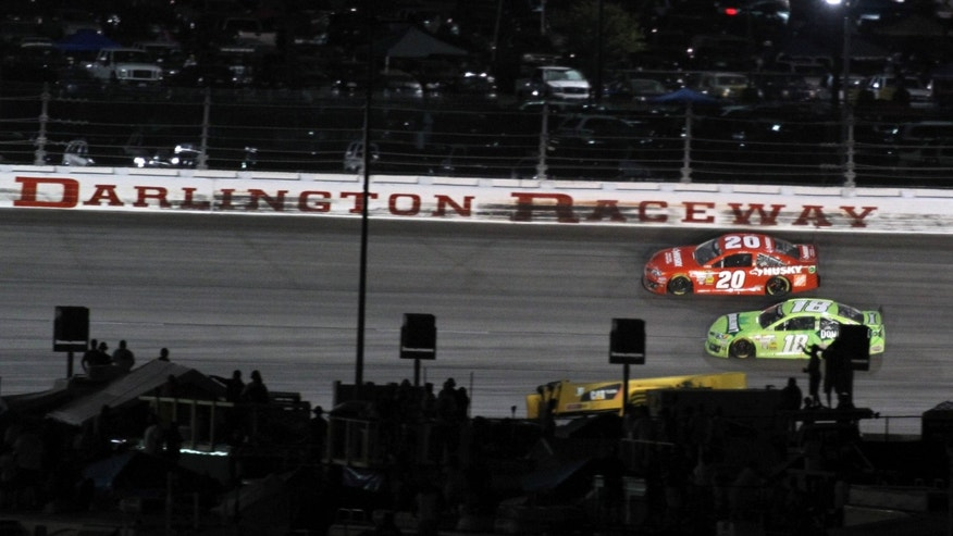 Matt Kennseth (20) passes Kyle Busch (18) on the back stretch on lap 355 on Saturday, May 11, 2013 at the NASCAR Sprint Cup series auto race in Darlington, S.C.  (AP Photo/Willis Glassgow)