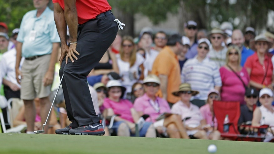 Tiger Woods reacts to a missed birdie putt on the third hole during the final round of The Players championship golf tournament at TPC Sawgrass, Sunday, May 12, 2013, in Ponte Vedra Beach, Fla.  (AP Photo/John Raoux)