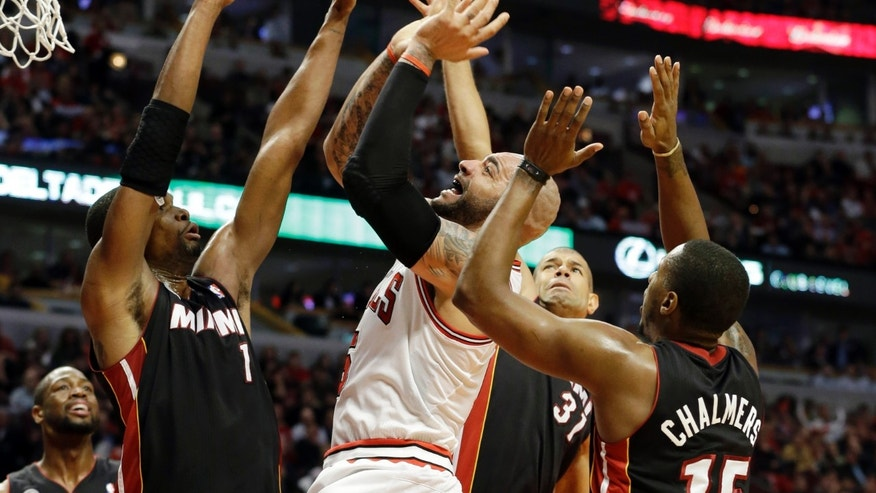 Miami Heat's Chris Bosh (1), Shane Battier (31) and Mario Chalmers (15) defend against Chicago Bulls forward Carlos Boozer (5) during the second half of Game 4 of an NBA basketball playoffs Eastern Conference semifinal on Monday, May 13, 2013, in Chicago. (AP Photo/Nam Y. Huh)