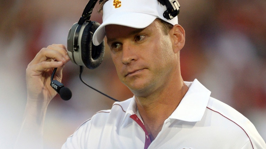 FILE - In this Oct. 20, 2012 file photo, Southern California head coach Lane Kiffin removes his headset during the second half of an NCAA college football game against Colorado, in Los Angeles. Southern California is coming off a historically disappointing season that has put Kiffin in precarious situation heading into his fourth season as Trojans coach. The Trojans will have a new quarterback and are still dealing with a roster limited by NCAA sanctions. They won't enter the season No. 1 like last year. Expectations are far more modest, which both Kiffin and his boss, athletic director Pat Haden, say is a good thing. (AP Photo/Mark J. Terrill, File)