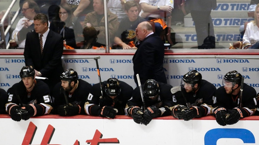 Anaheim Ducks head coach Bruce Boudreau, top center, wipes his face as team members look on during the third period in Game 7 of their first-round NHL hockey Stanley Cup playoff series against the Detroit Red Wings in Anaheim, Calif., Sunday, May 12, 2013. (AP Photo/Chris Carlson)