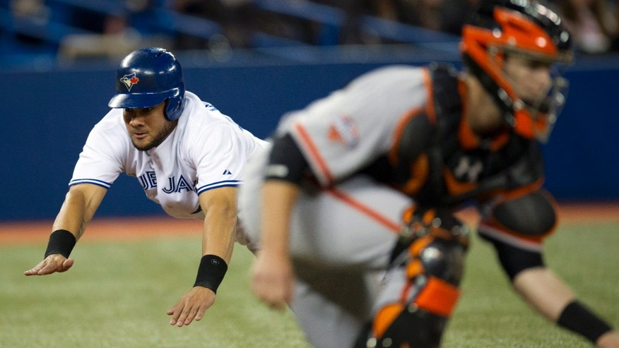 Toronto Blue Jays' Melky Cabrera dives into home plate to score behind San Francisco Giants catcher Buster Posey during the first inning of a baseball game Tuesday, May 14, 2013, in Toronto. (AP Photo/The Canadian Press, Frank Gunn)