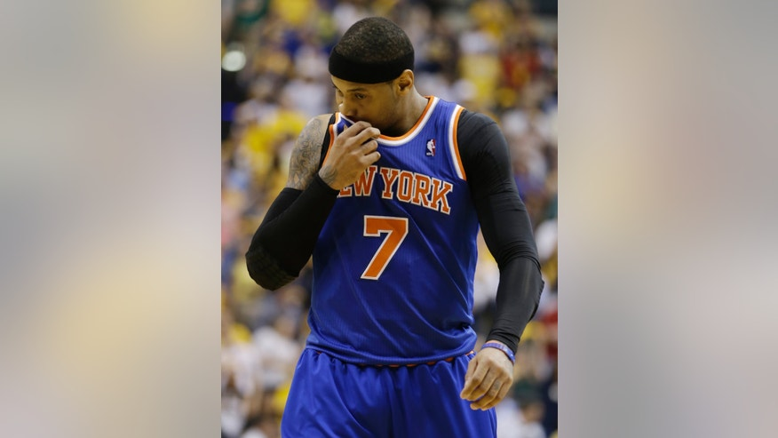 New York Knicks' Carmelo Anthony wipes his face as he leaves the court following the first half of Game 4 of an Eastern Conference semifinal NBA basketball playoff series against the Indiana Pacers, on Tuesday, May 14, 2013, in Indianapolis. (AP Photo/Darron Cummings)