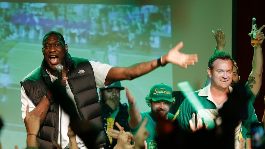 Former Seattle SuperSonics NBA basketball player Shawn Kemp, left, helps rally the crowd, Monday, May 13, 2013, at a rally in Seattle. Fans gathered to show their support for an effort by a group led by Seattle investor Chris Hansen to buy the Sacramento Kings and move them to Seattle. (AP Photo/Ted S. Warren)