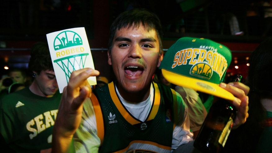 "A fan holds a Seattle SuperSonics NBA basketball cap and a sign that reads ""robbed,"" as he attends a fan rally Monday, May 13, 2013, in Seattle. Fans gathered to show their support for an effort by a group led by Seattle investor Chris Hansen to buy the Sacramento Kings and move them to Seattle. Fans designed the ""robbed"" signs after the Sonics were sold in 2006 and moved to Oklahoma City. (AP Photo/Ted S. Warren)"