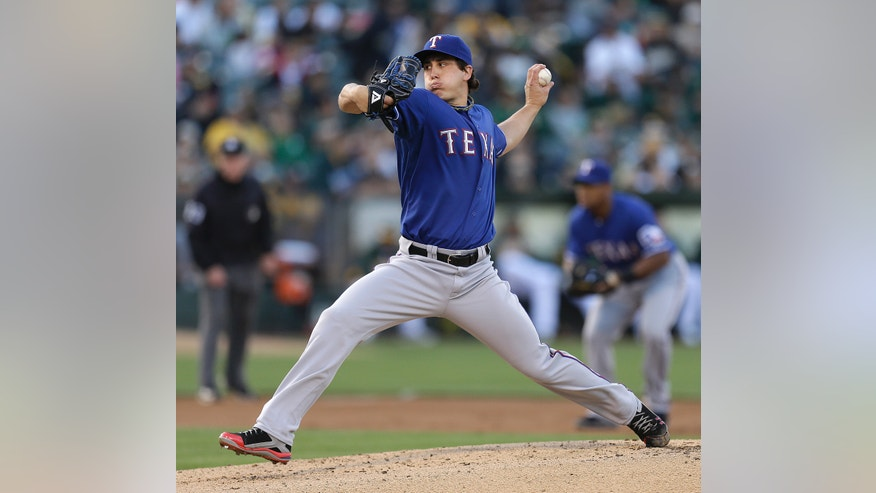 Texas Rangers pitcher Derek Holland works against the Oakland Athletics in the first inning of a baseball game Tuesday, May 14, 2013, in Oakland, Calif. (AP Photo/Ben Margot)