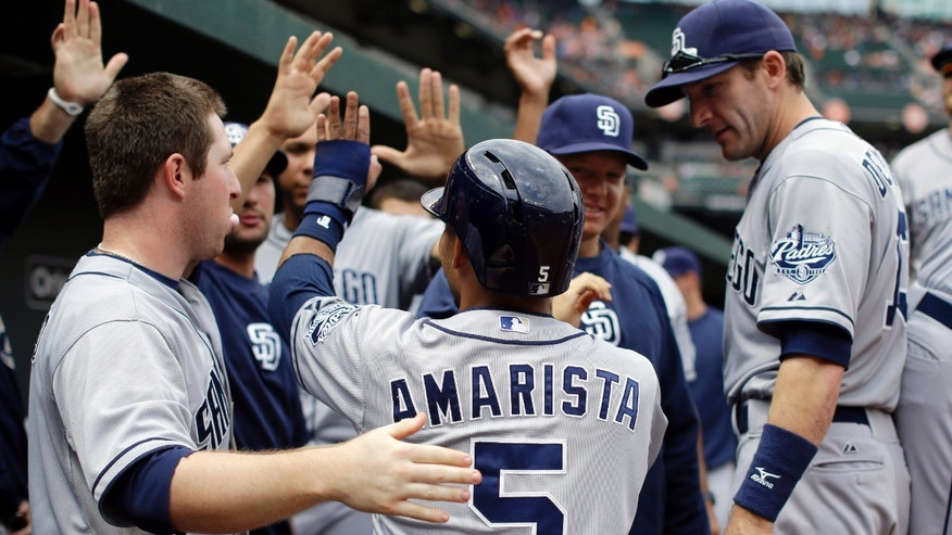 San Diego Padres' Alexi Amarista (5) high-fives teammates in the dugout after scoring on a double by Will Venable in the fourth inning of an interleague baseball game against the Baltimore Orioles in Baltimore, Wednesday, May 15, 2013. (AP Photo/Patrick Semansky)