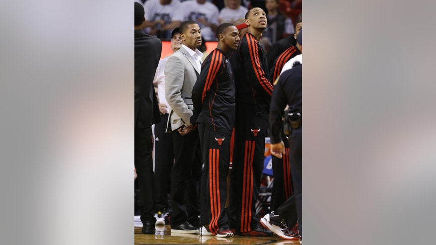 Chicago Bulls' Derrick Rose, left, stands with teammates during the second half of Game 5 of an NBA basketball Eastern Conference semifinal against the Miami Heat on Wednesday, May 15, 2013, in Miami. (AP Photo/Wilfredo Lee)