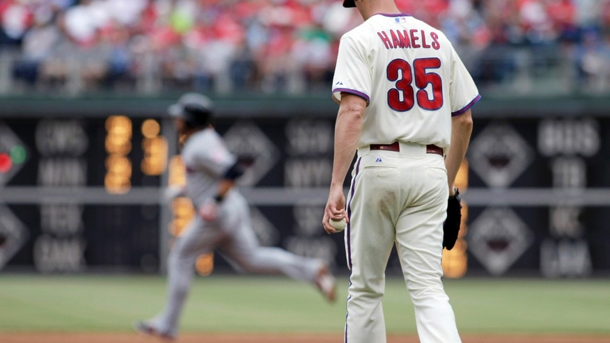 Philadelphia Phillies starting pitcher Cole Hamels walks back to the mound as Cleveland Indians' Mike Aviles round the bases after hitting a solo home run in the fourth inning of a interleague baseball game Wednesday, May 15, 2013, in Philadelphia. (AP Photo/H. Rumph Jr)
