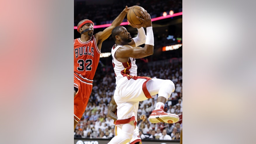 Miami Heat's Dwyane Wade, right, shoots as Chicago Bulls' Richard Hamilton (32) defends during the first half of Game 5 of an NBA basketball Eastern Conference semifinal, Wednesday, May 15, 2013, in Miami. (AP Photo/Wilfredo Lee)