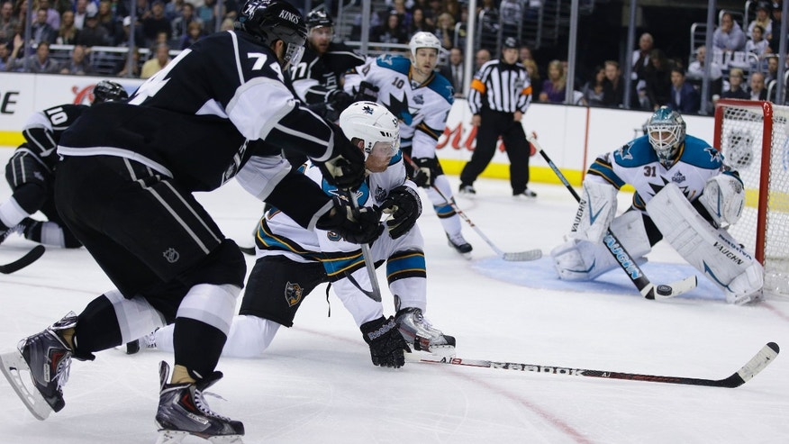 San Jose Sharks goalie Antti Niemi turns away a shot from Los Angeles Kings' Dwight King (74) as Sharks' Matt Irwin defends during the second period in Game 1 of a second-round NHL hockey Stanley Cup playoff series in Los Angeles, Tuesday, May 14, 2013. (AP Photo/Chris Carlson)