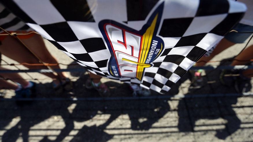 An Indianapolis 500 flag hangs near a group of school children hoping for a driver's autographs during practice for the Indianapolis 500 auto race at the Indianapolis Motor Speedway in Indianapolis, Wednesday, May 15, 2013. (AP Photo/Darron Cummings)