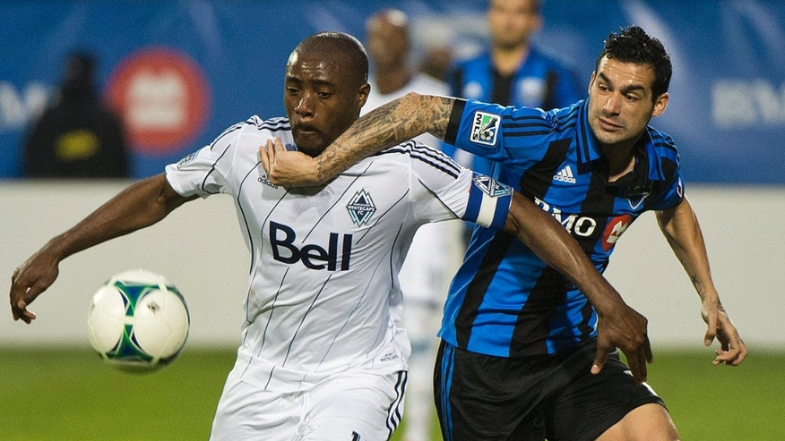 Montreal Impact's Andrés Romero, right, and Vancouver Whitecaps' Nigel Reo-Coker battle for the ball during first-half, first-leg action of the Canadian Championship soccer final  in Montreal, Wednesday, May 15, 2013. (AP Photo/The Canadian Press, Graham Hughes)
