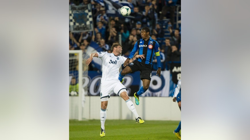 Montreal Impact's Patrice Bernier, right, and Vancouver Whitecaps' Brad Rusin go up for the ball during first-half, first-leg action of the Canadian Championship soccer final  in Montreal, Wednesday, May 15, 2013. (AP Photo/The Canadian Press, Graham Hughes)