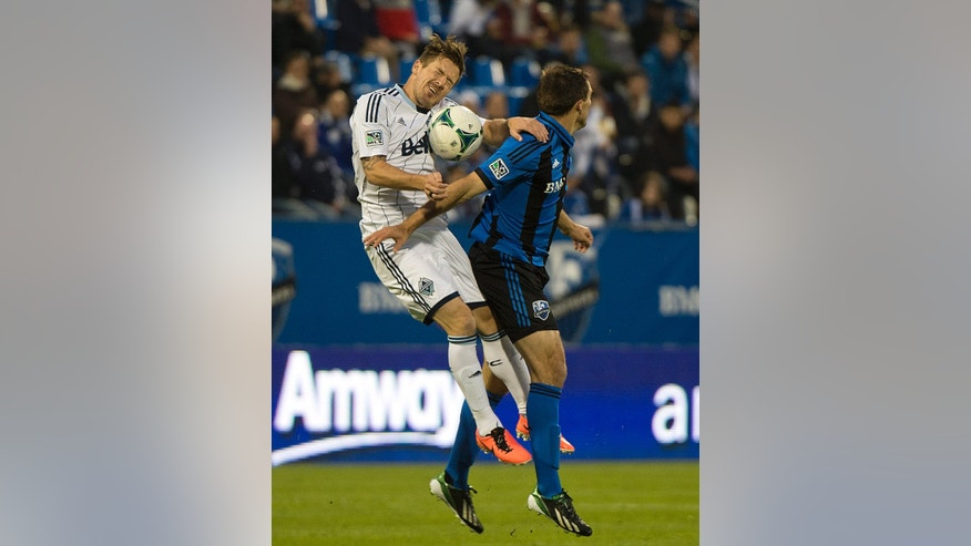 Montreal Impact's Andrew Wenger, right, and Vancouver Whitecaps' Jordan Harvey go up for the ball during first-half, first-leg action of the Canadian Championship soccer final  in Montreal, Wednesday, May 15, 2013. (AP Photo/The Canadian Press, Graham Hughes)
