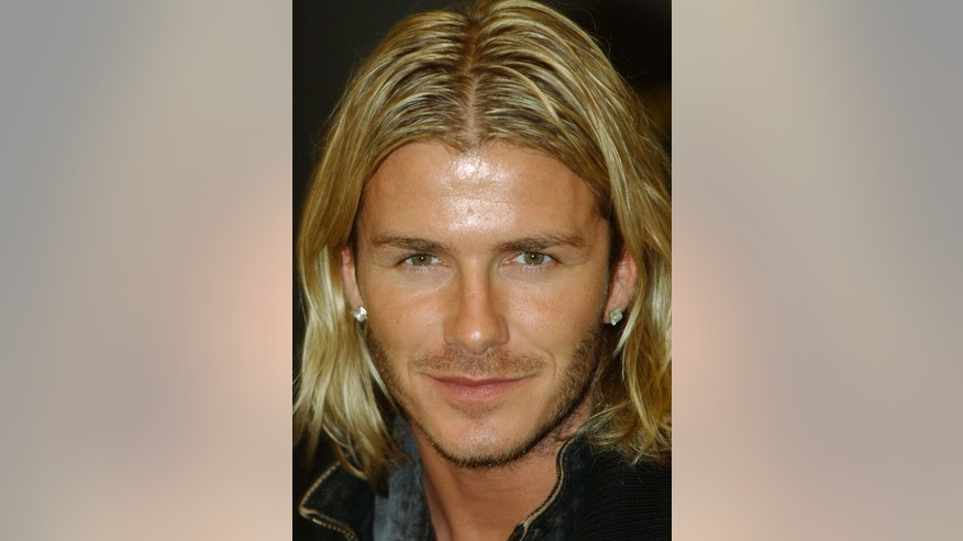 "FILE - In this Nov. 17, 2003 file photo,  soccer player David Beckham pauses during a signing session for his autobiography ""My Side"" held at a London bookstore. Beckham says he is retiring from soccer at the end of the season. The 38-year-old Beckham recently won a league title in a fourth country with Paris Saint-Germain. He has become a global superstar since starting his career at Manchester United. (AP Photo/Richard Lewis, FIle)"